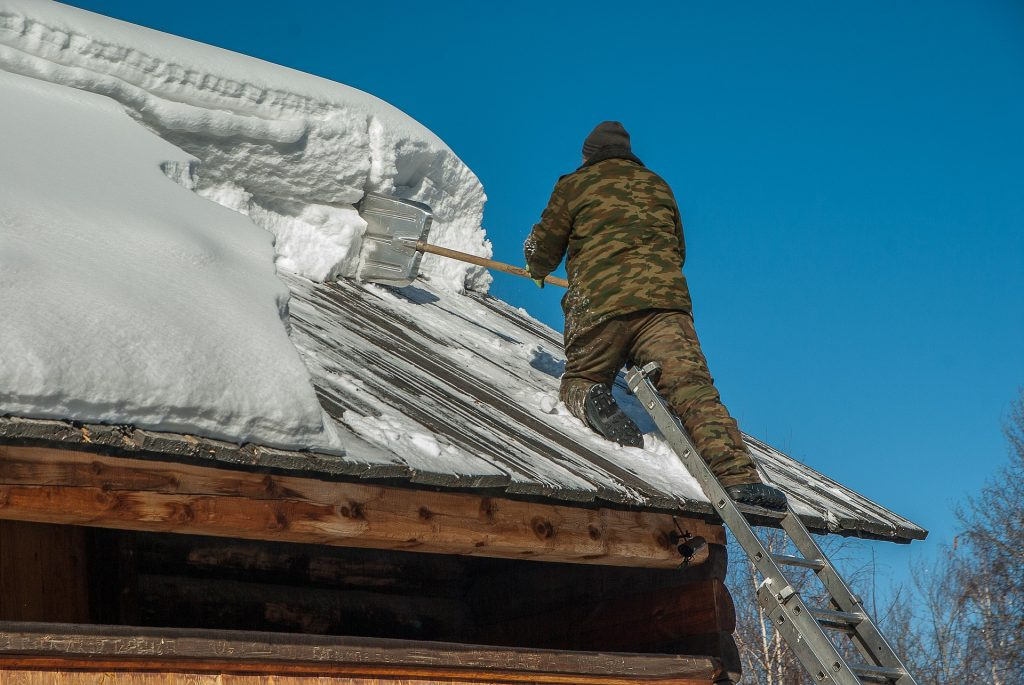 man removing snow off roof